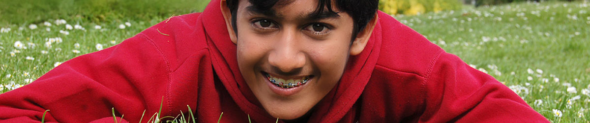 Boy with visible braces lying in a field