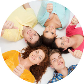 Group of young people lying in a circle giving thumbs up
